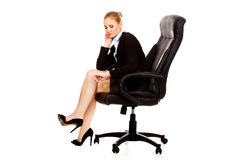 Tired or worried business woman sitting on armchair.  Stock Photo