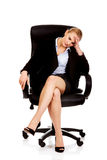 Tired or worried business woman sitting on armchair Stock Images