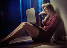 Tired wwoman using a laptop by night Stock Images