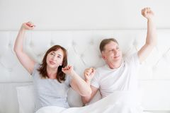 Tired yawn middle age couple in bed. Blank template t shirt. Family life and healthy relationships. Health care and morning. Concept. Copy space royalty free stock photo