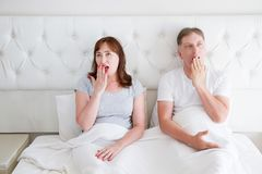 Tired yawn middle age couple in bed. Family life and healthy relationships. Health care and morning concept. Copy space.  stock photo