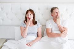 Tired yawn middle age couple in bed. Family life and healthy relationships. Health care and morning concept. Copy space.  royalty free stock photos