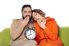 Tired yawning couple sitting on sofa holding big alarm clock. Tired yawning young couple in home clothes sitting on sofa holding big alarm clock stock images
