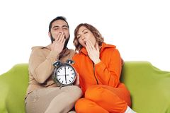 Tired yawning couple sitting on sofa holding big alarm clock. Tired yawning young couple in home clothes sitting on sofa holding big alarm clock royalty free stock image