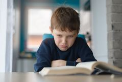 Tired 8 years old boy doing his homework at the table. Child reading a book at the desk Royalty Free Stock Images