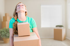 Tired Young Adult Woman Holding Moving Boxes In Empty Room In A Royalty Free Stock Photo