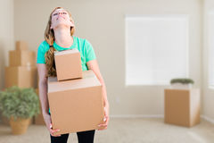 Tired Young Adult Woman Holding Moving Boxes In Empty Room In A Stock Images