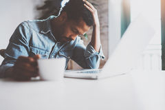 Tired young African man using laptop while sitting at the table on a sunny morning.Concept of people working hard home Stock Photos