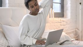 Tired Young African Woman with Neck Pain Working on Laptop in Bed stock footage
