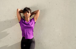 Tired young african woman relaxing to a wall outdoors after workout. Portrait of tired young african woman relaxing to a wall outdoors after workout Stock Photography