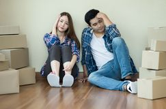 Tired Young Asian couple sitting with cardboard boxes In their n stock photos