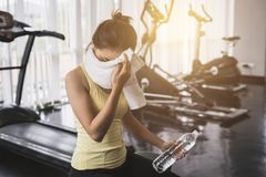 Tired young asian woman wiping face after work out stock photography