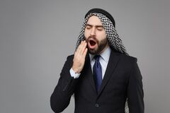 Tired young bearded arabian muslim businessman in keffiyeh kafiya ring igal agal classic suit isolated on gray