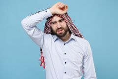 Tired young bearded arabian muslim man in keffiyeh kafiya ring igal agal casual clothes isolated on pastel blue