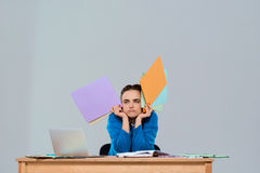 Tired young beautiful businesswoman sitting at workplace, holding colorful folders. Royalty Free Stock Images
