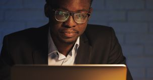Tired young black businessman working with laptop at night office. Freelancer working late in dark room office overtime stock video