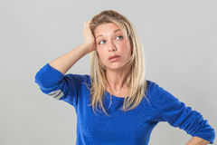 Tired young blond woman with bags touching her head Royalty Free Stock Images