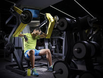 Tired young  bodybuilder doing weight lifting in gym. Stock Photography