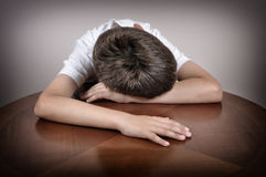 Tired young boy. Sitting and sleeping with his head and hands on the brown table Royalty Free Stock Image