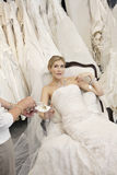 Tired young bride in wedding dress sitting while mother showing footwear Royalty Free Stock Photography