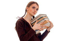 Tired young brunette student girl in brown sport clothes with a lot of books in her hands posing isolated on white Royalty Free Stock Images