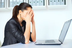 Tired young business woman with laptop Royalty Free Stock Photo