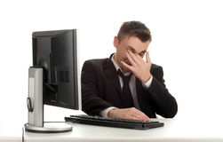 Tired young businessman with computer Stock Photography