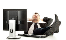 Tired young businessman with computer Royalty Free Stock Photography