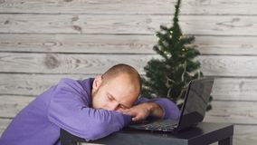 Tired young businessman in office on new year eve. Christmas tree in office. Laptop on desk. Business Concept. Man in stock video