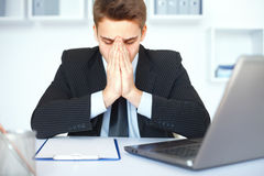 Tired young businessman in office Royalty Free Stock Image