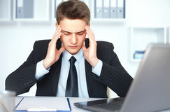 Tired young businessman in office Royalty Free Stock Images
