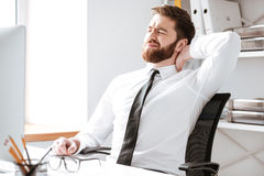 Tired young businessman in office stretching. Royalty Free Stock Photos