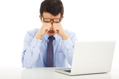 Tired young businessman rubbing his eyes. In office royalty free stock image