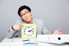 Tired young businessman showing finger on clock Stock Photos