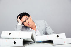 Tired young businessman sitting at the table Royalty Free Stock Photo