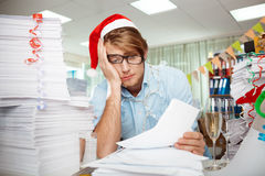 Tired young businessman sitting at workplace among papers on christmas day. Stock Photo