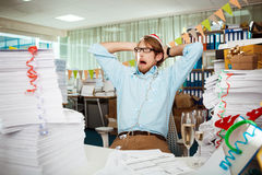 Tired young businessman sitting at workplace among papers on christmas day. Stock Photography