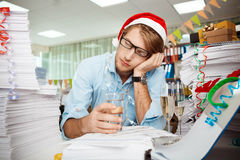 Tired young businessman sitting at workplace among papers on christmas day. Royalty Free Stock Photos