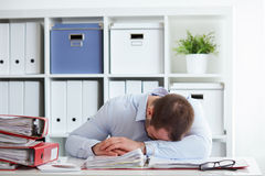 Tired young businessman sleeping royalty free stock photography