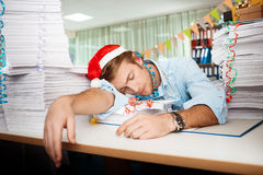 Tired young businessman sleeping at workplace among papers on christmas day. Stock Images