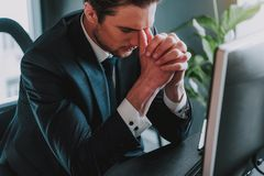 Tired young businessman touching his face and closing eyes royalty free stock image
