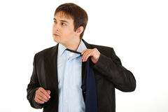 Tired young businessman untying his tie Stock Photography