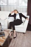 tired young businesswoman in formal wear sleeping on armchair in hotel stock photography