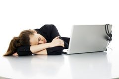 Tired young businesswoman with laptop Stock Image