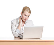Tired young businesswoman sitting at a office desk with laptop Royalty Free Stock Photos