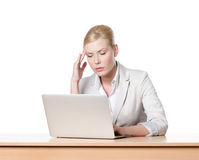 Tired young businesswoman sitting at a table with laptop Royalty Free Stock Images