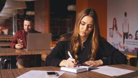 Tired young businesswoman sitting at the table with lnotebook. Tired young businesswoman sitting at the table with notebook,girl sits in cafe. This woman is stock video footage