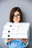 Tired young businesswoman standing with folders Royalty Free Stock Photos