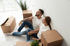 Tired couple sitting leaning back against wall in new apartment. Tired young couple sitting leaning back against wall with closed eyes in new apartment with stock photos