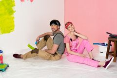 Tired young couple in working overalls sitting on floor surrounded by painting. Tools royalty free stock image